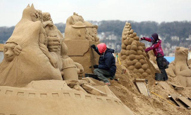 A sand sculptor works on a Toy Story themed sand sculpture as pieces are prepared as part of this year's Hollywood themed annual Weston-super-Mare Sand Sculpture festival on March 26, 2013 in Weston-Super-Mare, England. Due to open on Good Friday, currently twenty award winning sand sculptors from across the globe are working to create sand sculptures including Harry Potter, Marilyn Monroe and characters from the Star Wars films as part of the town's very own movie themed festival on the beach.  (Photo by Matt Cardy)