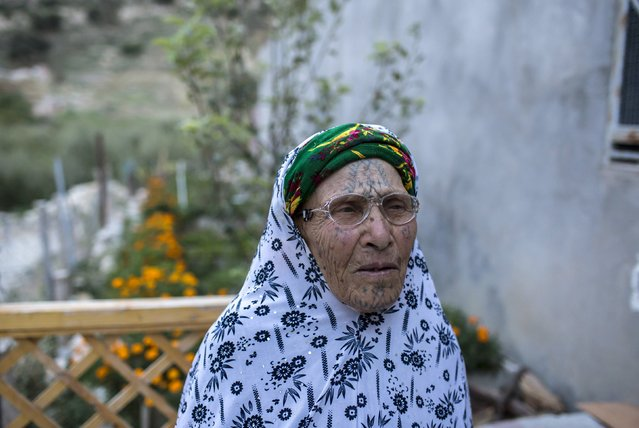 Djemaa Daoudi, 90, a berber woman from the Chaouia region, who has facial tattoos, sits outside her house in Inoughissen in the Aures Mountain near the eastern city of Batna, Algeria October 8, 2015. Daoudi was forced to have a tattoo by her husband just after their wedding when she was 15 years old because it was a fashion. A local Berber woman tattooed her. Some believers have told these Muslim women that by allowing the tattoos they committed a sin according to Islam. Today Daoudi regrets being tattooed. (Photo by Zohra Bensemra/Reuters)