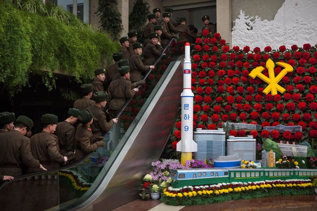 North Korean soldiers ride an escalator past a model of their country's Unha Rocket as they enter an exhibition in Pyongyang on Sunday, February 17, 2013 where Kimjongilia flowers, named after the late North Korean leader Kim Jong Il, were on display. (Photo by David Guttenfelder/AP Photo)
