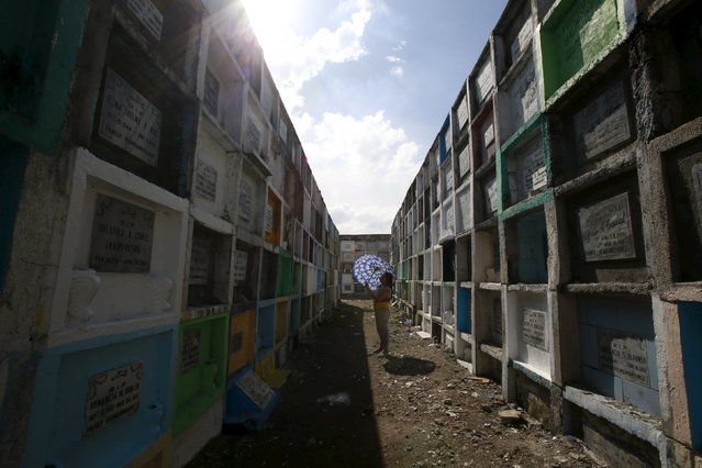 """A woman offers prayers in front of the tomb of her departed relative buried in an """"apartment-style"""" grave inside a cemetery in Navotas city, north of Manila October 31, 2015. (Photo by Romeo Ranoco/Reuters)"""