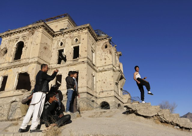 Abbas Alizada, who calls himself the Afghan Bruce Lee (R), poses for the media in front of the destroyed Darul Aman Palace in Kabul December 9, 2014. (Photo by Mohammad Ismail/Reuters)