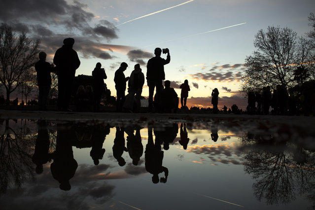 People are reflected in a puddle as they take photographs at the Temple of Debod public park, during sunset in Madrid, Wednesday, December 27, 2017. The park is frequented by locals but also attracts tourists due to its open view at sunset. (Photo by Francisco Seco/AP Photo)