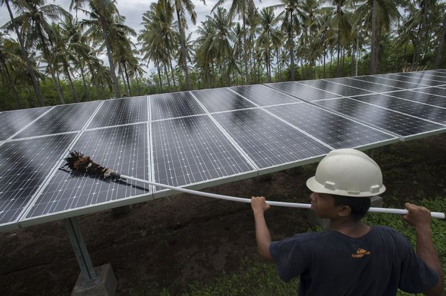 An employee of PT Perusahaan Listrik Negara (PLN) cleans the surface of solar panels at a solar power generation plant in Gili Meno island, in this December 9, 2014 photo taken by Antara Foto. PT PLN is developing new renewable energy on three islands, Gili Air, Gili Meno and Gili Trawangan to replace diesel generators. (Photo by Widodo S. Jusuf/Reuters/Antara Foto)