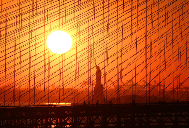 People walk across the Brooklyn Bridge as the sun sets behind the Statue of Liberty on November 4, 2020 in New York City. (Photo by Gary Hershorn/Getty Images)