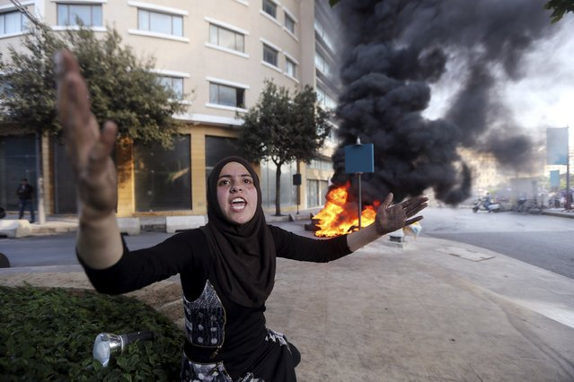 Wadha al-Sayyed, wife of captive Lebanese soldier Khaled Moqbel, protests for his release and government action, near burning tyres blocking a road in Beirut, December 15, 2014. More than two dozen members of the Lebanese security forces are being held by Sunni Islamists. (Photo by Hasan Shaaban/Reuters)