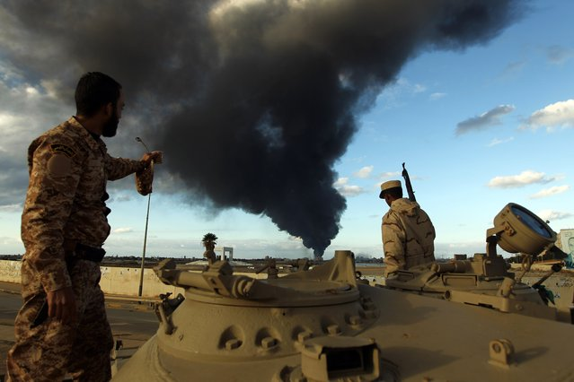 Members of the Libyan army stand on a tank as heavy black smoke rises from the city's port in the background after a fire broke out at a car tyre disposal plant during clashes against Islamist gunmen in the eastern Libyan city of Benghazi on December 23, 2014. (Photo by Abdullah Doma/AFP Photo)