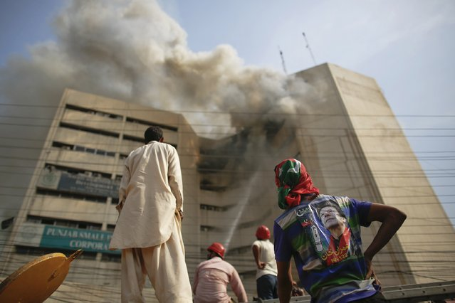 A man (R) with a pre-election poster of Imran Khan, Pakistani cricketer turned politician, watches firefighters trying to put away fire from a burning building in central Lahore May 9, 2013. Fire erupted on the seventh floor of the LDA Plaza in Lahore and quickly spread to higher floors leaving many people trapped inside the building. At least three people fell from the high floors trying to avoid the fire that engulfed the building, local media reports. (Photo by Damir Sagolj/Reuters)