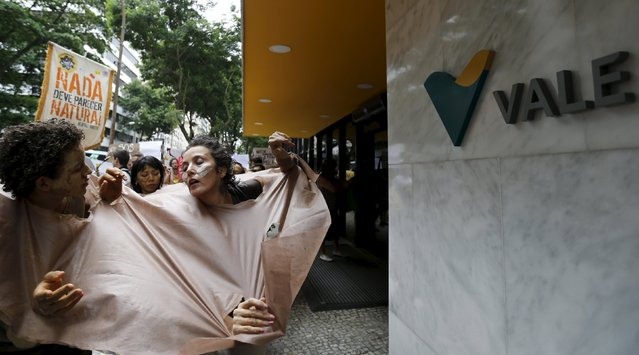 Environmental activists perform during a protest in front of the headquarters of Brazilian mining company Vale SA in downtown Rio de Janeiro, Brazil, November 16, 2015. The collapse of two dams at a Brazilian mine, owned by Vale SA and BHP Billiton Ltd, has cut off drinking water for quarter of a million people and saturated waterways downstream with dense orange sediment that could wreck the ecosystem for years to come. (Photo by Sergio Moraes/Reuters)