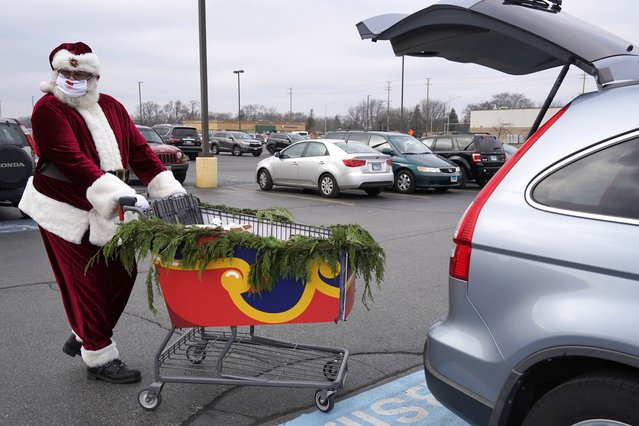 Santa Claus wears a mask as he pushes a sleigh full of curbside grocery orders to an Aldi customer at a parking lot in Palatine, Ill., Saturday, December 19, 2020. For this weekend only, Santa Claus is delivering groceries to Aldi customers in Palatine and several other towns in the Chicago area. (Photo by Nam Y. Huh/AP Photo)