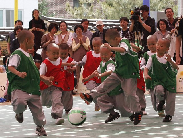 Shaven-headed young boys play the Dongjasung (little monk) soccer match to celebrate Buddha's upcoming birthday on May 17 at Jogye temple in Seoul, South Korea, Tuesday, May 14, 2013. The children entered the temple to have an experience of monks' life for two weeks, called Little Buddha Camp. (Photo by Ahn Young-joon/AP Photo)
