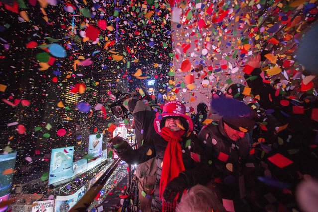 Revellers toss confetti over Times Square from a hotel after the clock struck midnight during New Year's Eve celebrations in New York January 1, 2015. (Photo by Keith Bedford/Reuters)