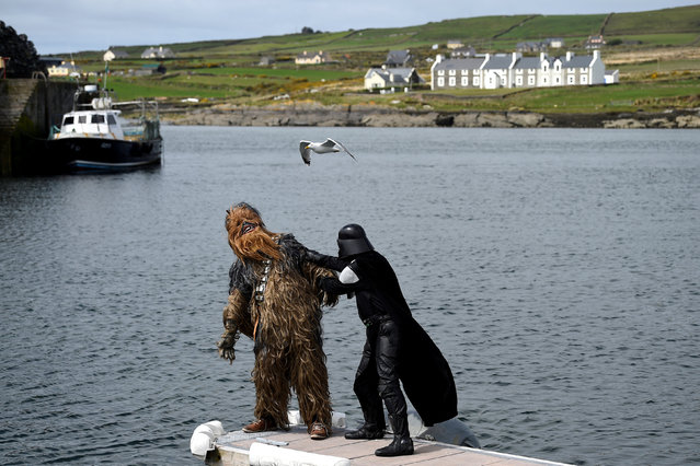 """Star Wars fans dressed in costume as a Chewbacca and a Shadow Stormtrooper engage in a mock fight before boarding a boat for a trip to Skellig Island during the inaugural """"May The 4th Be With You"""" festival in the County Kerry village of Portmagee, Ireland, May 4, 2018. (Photo by Clodagh Kilcoyne/Reuters)"""