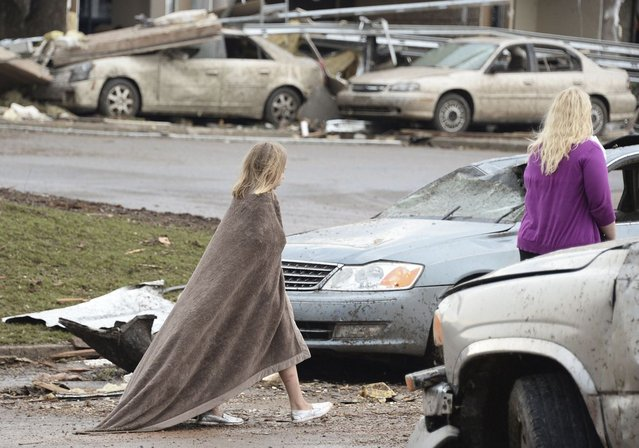 A girl tries to keep warm near the Moore Hospital after being hit tornado that destroyed buildings and overturned cars in Moore, Oklahoma, May 20, 2013. (Photo by Gene Blevins/Reuters)