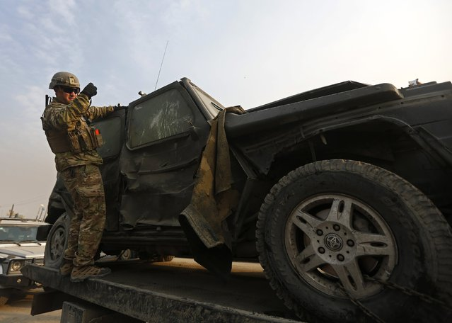 A U.S. soldier investigates the wreckage of a European Union vehicle which was hit by a suicide attack in Kabul January 5, 2015. At least one person was killed and five other were wounded police officials said. (Photo by Omar Sobhani/Reuters)