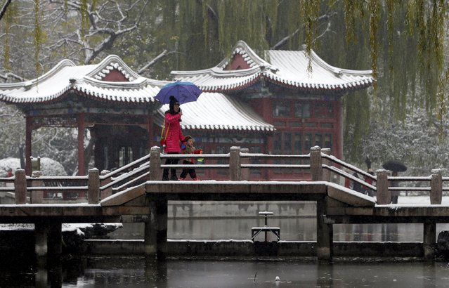 A woman and her son enjoy the snow scene at a park in central Beijing, China, November 22, 2015. (Photo by Jason Lee/Reuters)