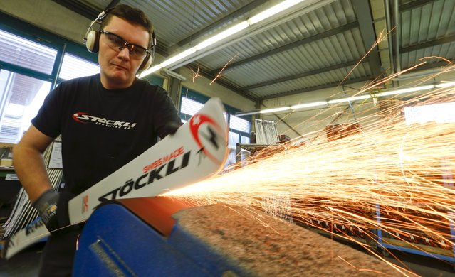Sparks are thrown as an employee grinds the edges of a ski at the plant of Swiss ski manufacturer Stoeckli in Malters, Switzerland November 25, 2015. (Photo by Arnd Wiegmann/Reuters)