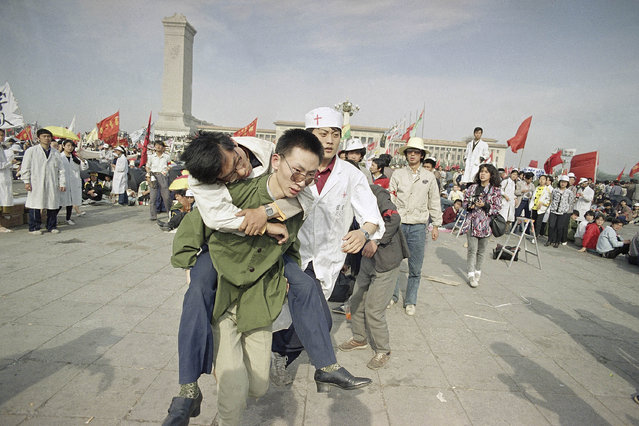 In this May 16, 1989 file photo, medics rush a Beijing university student from Tiananmen Square after he collapsed on the third day of a hunger strike in Beijing. A quarter century after the Communist Party's attack on demonstrations centered on Tiananmen Square on June 4, 1989, the ruling party prohibits public discussion and 1989 is banned from textbooks and Chinese websites. (Photo by Sadayuki Mikami/AP Photo)