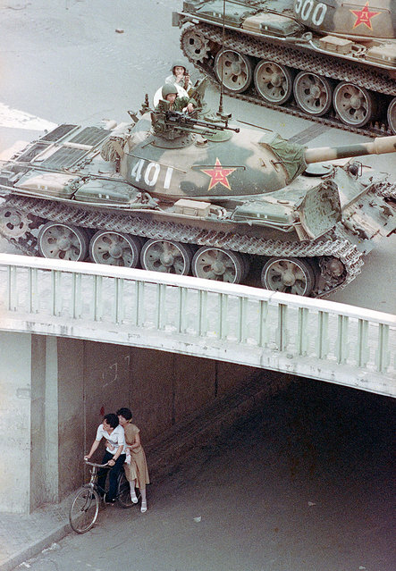 A Chinese couple on a bicycle take cover beneath an underpass as tanks deploy overhead in eastern Beijing, on June 5, 1989. (Photo by Liu Heung Shing/AP Photo)