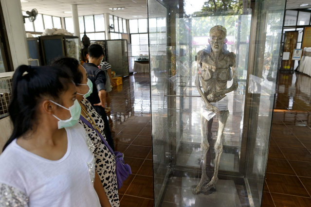 A picture made available 30 November 2015 shows Thai visitors looking at the preserved body of a deceased AIDS patient at a museum at the Buddhist temple Wat Phra Baat Namphu, which is known for its humanitarian treatment of HIV positive and AIDS sick patients, in Lopburi province, 150 km north of Bangkok, Thailand, 29 November 2015. The Temple's AIDS hospice is the largest of its kind in Thailand, providing care for HIV positive patients as well as people living with AIDS. (Photo by Diego Azubel/EPA)