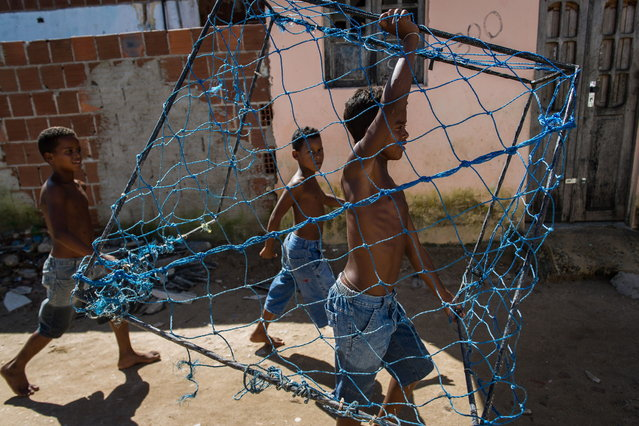 A boy carries a handmade goal as he heads to play football in a shantytown of Olinda, about 18 km from Recife in northeastern Brazil, on June 18, 2013 as the FIFA Confederations Cup Brazil 2013 football tournament is being held in the country. The historic centre of Olinda is listed as an UNESCO World Heritage Site. (Photo by Yasuyoshi Chiba/AFP Photo)