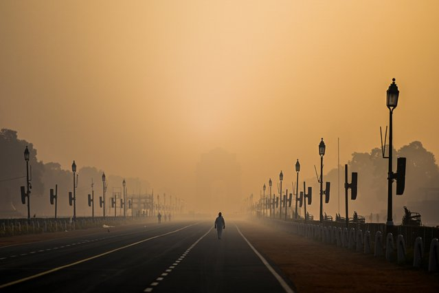 A man walks along Rajpath amid smoggy conditions in New Delhi on January 28, 2021. (Photo by Jewel Samad/AFP Photo)