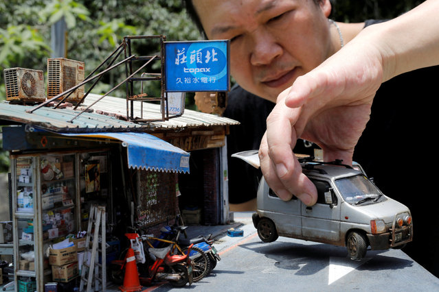 Taiwanese artist Hank Cheng poses with his miniature model of Taipei street scenes, in New Taipei City, Taiwan on June 17, 2018. (Photo by Tyrone Siu/Reuters)