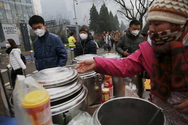 "Morning commuters wearing protective masks to shield from extreme smog pass by a food vendor in central Beijing December 8, 2015 as China's capital issues its first ever ""red alert"" for pollution. (Photo by Damir Sagolj/Reuters)"