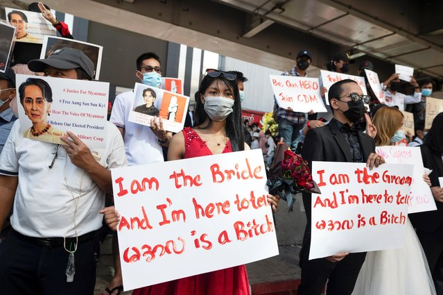 Demonstrators wearing wedding clothes hold up placards as they rally against the military coup in Yangon, Myanmar, February 10, 2021. (Photo by Reuters/Stringer)
