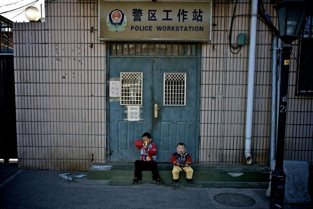 """Guarding a Police Workstation"". 2 small boys playing outside a local police station. Location: Shong Shu Jie, Beijing, China. (Photo and caption by Ben Longland/National Geographic Traveler Photo Contest)"