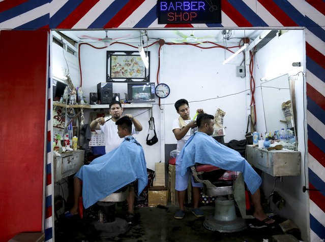 Filipino men get a haircut inside a barber shop near the Balintawak public market in metropolitan Manila, Philippines on Friday, April 20, 2018. Balintawak is a popular market where goods can be bought for a cheaper price. (Photo by Aaron Favila/AP Photo)