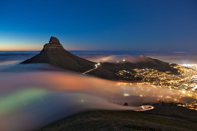 """""""Cape Town Fog"""". Taken one evening in April 2013 this long-exposure image shows a bank of fog rolling off the Atlantic Ocean, over Kloof Nek & Signal Hill and into the city of Cape Town, South Africa. (Photo and caption by Eric Nathan/National Geographic Traveler Photo Contest)"""