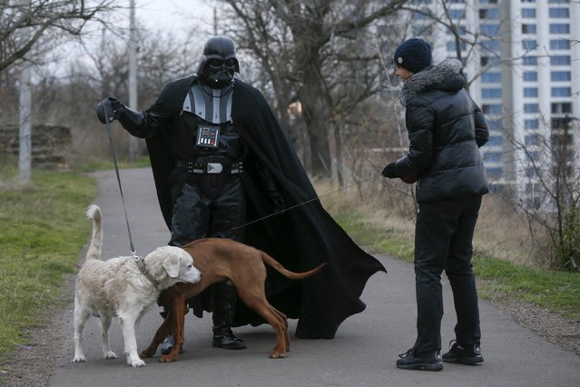 Darth Mykolaiovych Vader, who is dressed as the Star Wars character Darth Vader, poses for a picture as he speaks to a woman while walking his dog in a park in Odessa, Ukraine, December 3, 2015. (Photo by Valentyn Ogirenko/Reuters)