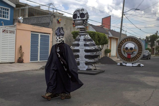 """A disguised person walks among the monumental skulls installed as part of the """"Day of the Dead"""" celebration at Santa Cecilia, Tlahuac on November 1, 2020 in Mexico City, Mexico. Known as one of the most representative traditions in Mexico, the day of the dead takes place during November 1 and 2 when peole remember those who have died with offerings, family gatherings and vistis to cemeteries. Due to the Covid-19 pandemic, massive celebrations are not allowed and graveyards will remain closed this year. (Photo by Cristopher Rogel Blanquet/Getty Images)"""