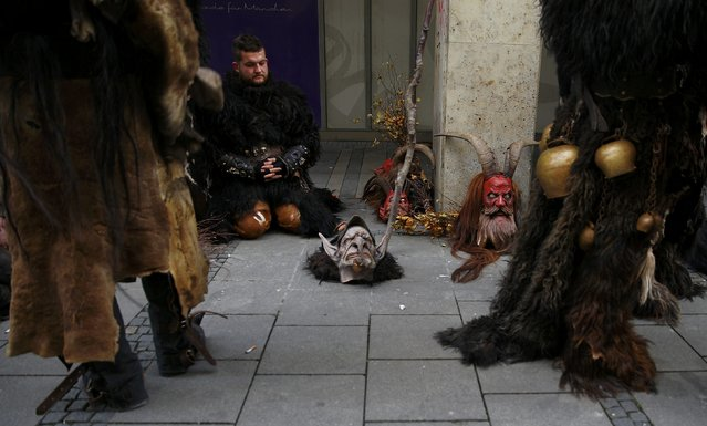Men dressed as 'Krampuss' prepare to parade at Munich's Christmas market, December 13, 2015. (Photo by Michael Dalder/Reuters)