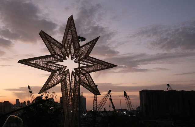 A star is seen on top of a Christmas tree near the grain silo that was damaged in a massive explosion at Beirut port, in Beirut, Lebanon on December 21, 2020. (Photo by Mohamed Azakir/Reuters)