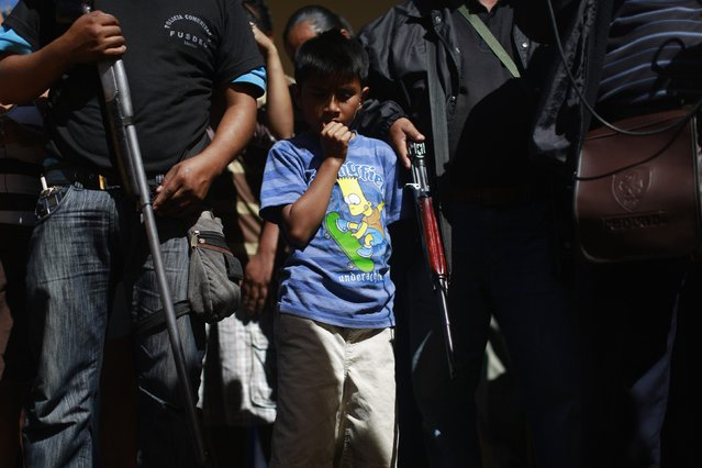 A boy stands amongst members of the Community Police of the FUSDEG (United Front for the Security and Development of the State of Guerrero) as he attends a presentation of weapons that were seized, in the village of Petaquillas, on the outskirts of Chilpancingo, in the Mexican state of Guerrero, February 1, 2015. (Photo by Jorge Dan Lopez/Reuters)