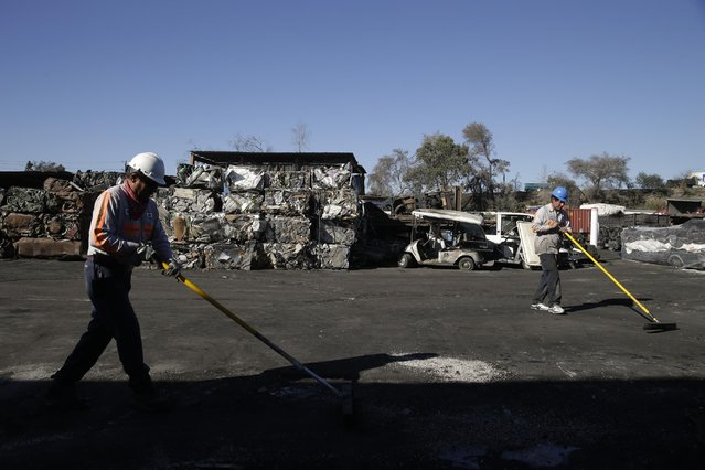 In this Wednesday, November 11, 2015 photo, Orlando Rodriguez, right, and Jose Garate sweep at Aadlen Brothers Auto Wrecking, also known as U Pick Parts, in the Sun Valley section of Los Angeles. (Photo by Jae C. Hong/AP Photo)