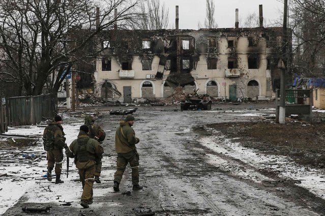 Members of the armed forces of the separatist self-proclaimed Donetsk People's Republic walk near a building destroyed during battles with the Ukrainian armed forces in Vuhlehirsk, Donetsk region, February 4, 2015. (Photo by Maxim Shemetov/Reuters)