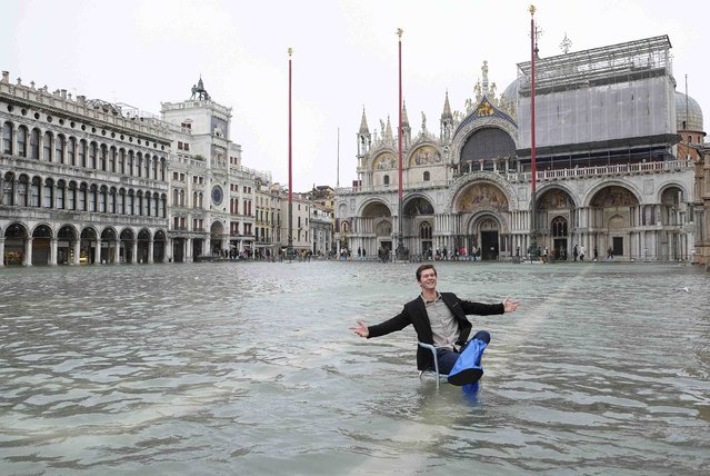 A man poses in a flooded St. Mark's Square during a period of seasonal high water in Venice, February 6, 2015. (Photo by Manuel Silvestri/Reuters)