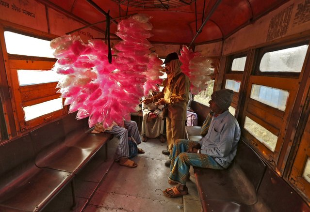 A conductor (C) collects fares from candy floss sellers as they travel in a tram to a marketplace early morning in Kolkata, India, December 23, 2015. (Photo by Rupak De Chowdhuri/Reuters)