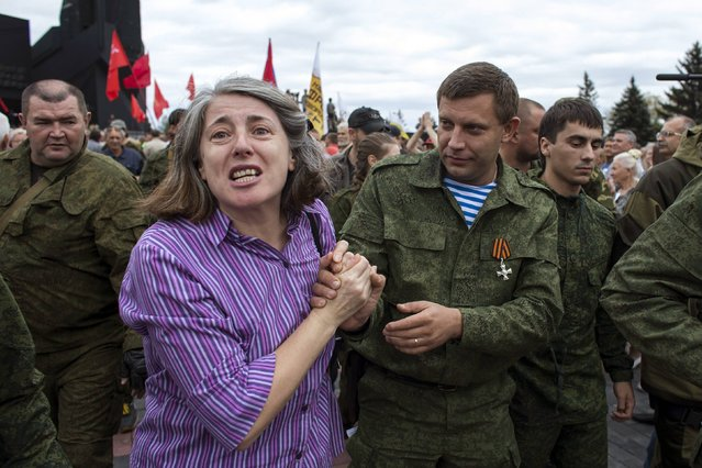 A woman holds the hand of the prime minister of the rebels' self-proclaimed Donetsk People's Republic (DNR), Alexander Zakharchenko (R), during a ceremony to honour the World War Two defenders of Donetsk from Nazi forces in Donetsk, in this September 8, 2014 file photo. (Photo by Marko Djurica/Reuters)