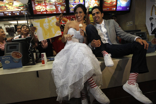 Fast-food fanatics Marisela Matienzo and Carlos Munoz pose for a picture after getting married at a McDonald's in the suburb of San Pedro Garza, neighbouring Monterrey November 26, 2010. The local franchise for McDonald's Corp said the wedding was the first in one of its outlets in Latin America. (Photo by Tomas Bravo/Reuters)