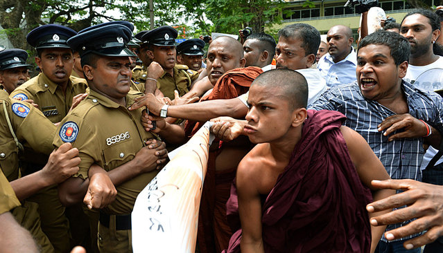 """A group of """"Power of Ravana"""" Buddhist monks push through police barricades to march during a demonstration outside the UN office in Colombo on August 26, 2013, denouncing human rights chief Navi Pillay on the first full day of her visit to Sri Lanka.  The UN's top rights official began her visit to Sri Lanka on August 25,  by brushing aside criticism that she overstepped her brief and vowing to raise human rights concerns with Colombo. (Photo by Ishara S. Kodikara/AFP Photo)"""