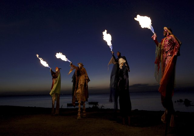 Members of the Kaisokah Moko Jumbies perform with fire on the waterfront near their San Fernando, Trinidad base February 10, 2015. (Photo by Andrea De Silva/Reuters)