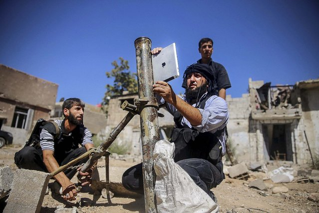 """A member of the """"Ansar Dimachk"""" Brigade, part of the """"Asood Allah"""" Brigade which operates under the """"Free Syrian Army"""", uses an iPad during preparations to fire a homemade mortar at one of the battlefronts in Jobar, Damascus September 15, 2013. (Photo by Mohamed Abdullah/Reuters)"""