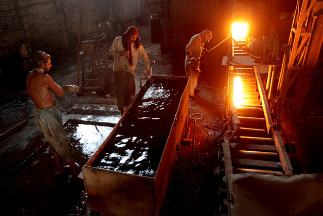 A worker whose shift ended bathes as another worker pulls a heated steel bar from the furnace at a steel mill in Islamabad, Pakistan November 11,  2016. (Photo by Caren Firouz/Reuters)
