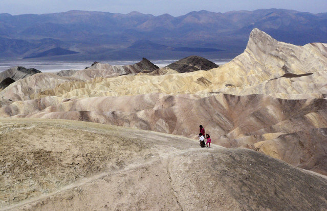 In this April 11, 2010 file photo, tourists walk along a ridge at Death Valley National Park, Calif. Preliminary data show that Death Valley set the world record for hottest month in July, 2018. National Weather Service meteorologist Todd Lericos says the month's average temperature at Furnace Creek in Death Valley was 108.1 degrees Fahrenheit (42.28 Celsius). That eclipses the previous record, set in Death Valley during July 2017 when the average was 107.4 degrees F (41.89 C). (Photo by Brian Melley/AP Photo)