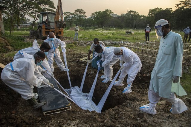 Relatives and municipal workers in protective suit bury the body of a person who died due to COVID-19 in Gauhati, India, Sunday, April 25, 2021. (Photo by Anupam Nath/AP Photo)