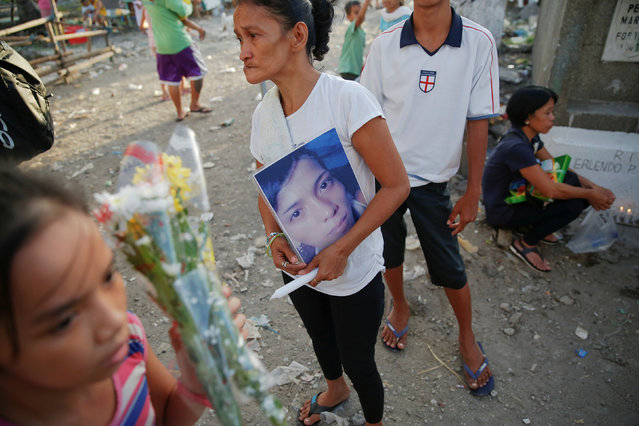 The mother of Angelo Lafuente, whose body, riddled with bullets, was found by a filthy river that feeds into the Manila bay, holds his picture as she visits his grave on the All Saints Day in Manila, Philippines November1, 2016. (Photo by Damir Sagolj/Reuters)
