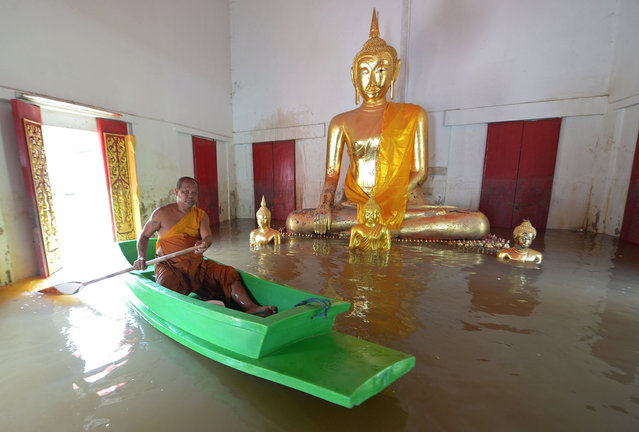 A buddhist monk paddles boat past a buddha statue at a temple in Ayutthaya province, north of Bangkok on October 3, 2013. The Disaster Prevention and Mitigation Department reported that 25 provinces in Thailand are still flooded and 27 people have died idue to the flood. (Photo by Pornchai Kittiwongsakul/AFP Photo)